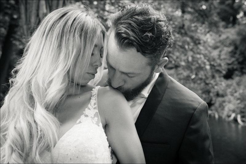 Le mariè embrasse l'épaule de la mariée