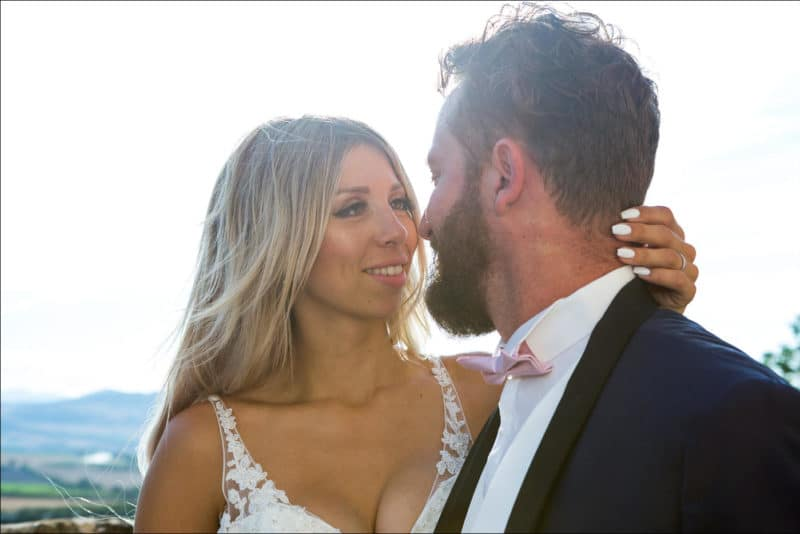 Photo en contre-jour avec les mariès se regardent dans les yeux