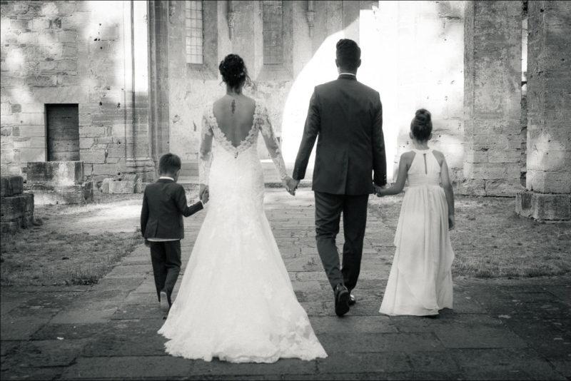 Les maris et leurs enfants marchent de dos en se tenant la main