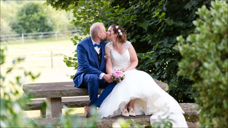 Les mariés s'embrassent, ils sont assis sur une table en bois