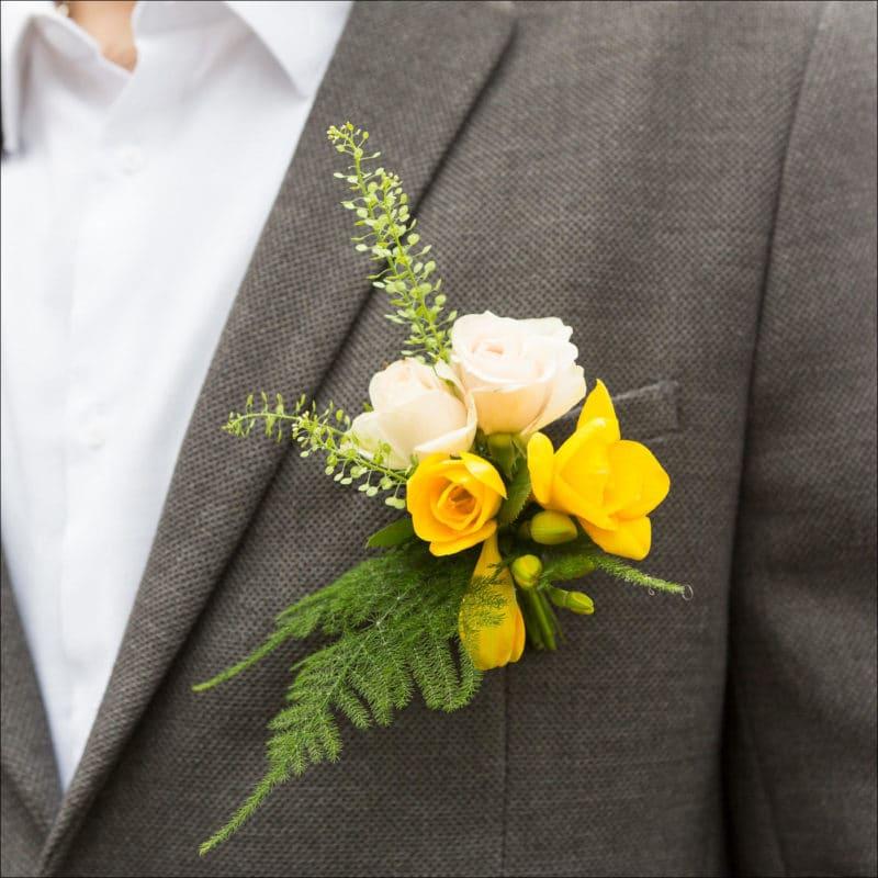 Gros plan sur la boutonnière fleurie du marié