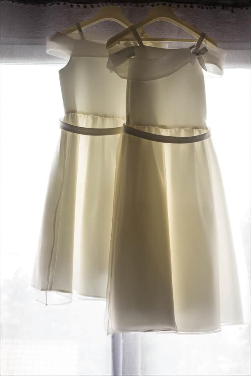 Les robes des filles de la mariée sont pendues sur un cintre, devant la fenêtre