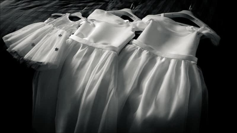 Les robes des filles de la mariée alignées sur le lit