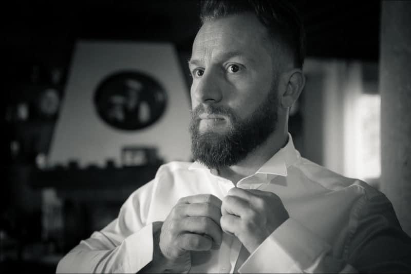 Le marié se prépare et boutonne sa chemise