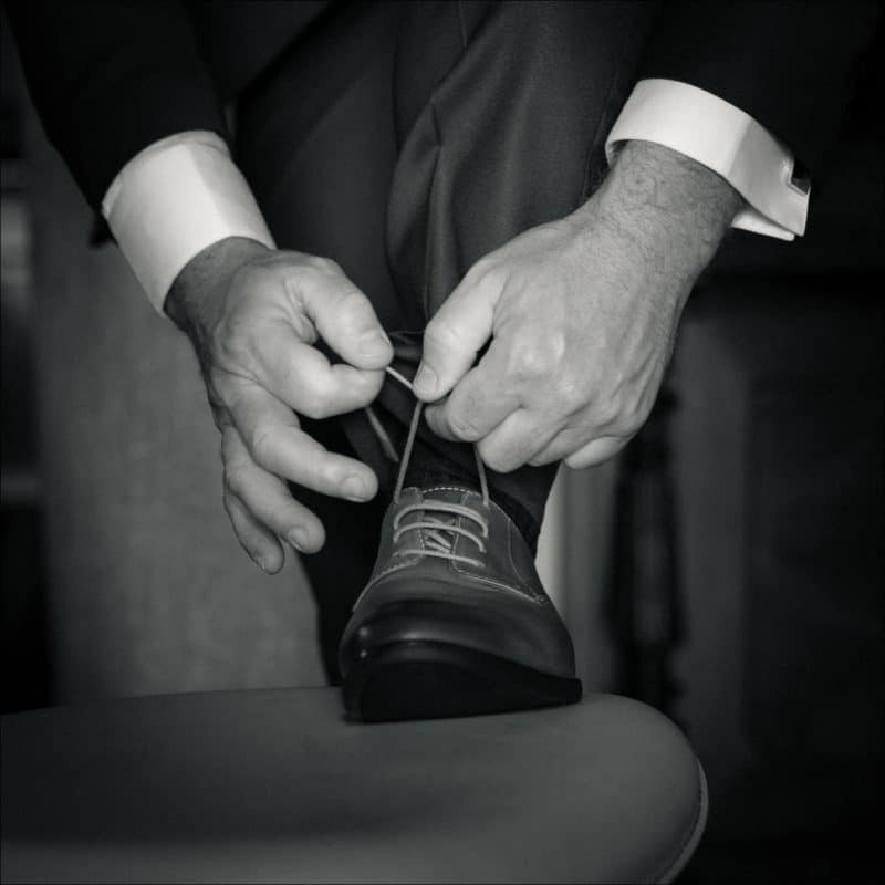 Le marié fait ses lacets de chaussure