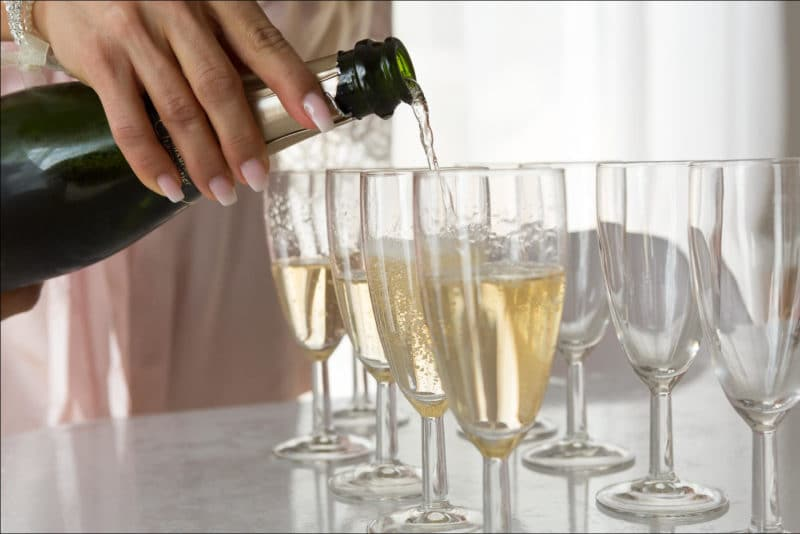 La marièe sert du champagne lors des préparatifs