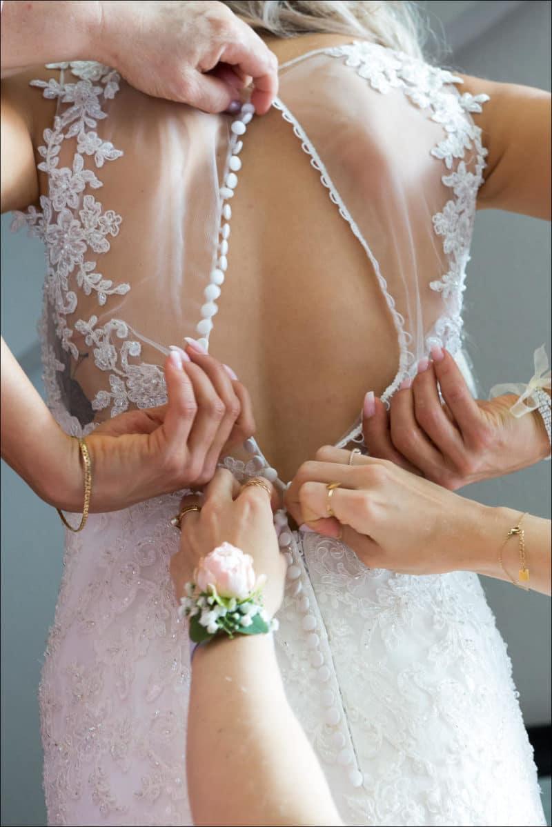 Les fille d'honneur boutonnent la robe de la mariée