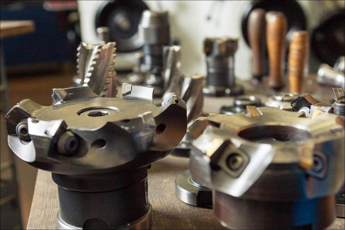 Des outillages d'usinage sont placés sur une déserte d'atelier